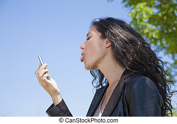sticking out tongue in video call - woman sticking out...