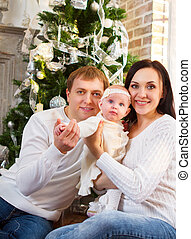Happy family with Christmas baby near the Christmas tree