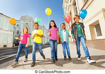 Walking children diversity with colorful balloons