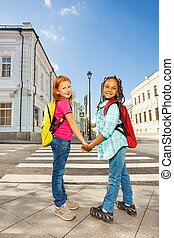 Two girls holding hands and standing near road - Two girls...