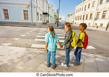 Three kids holding hands stand on street