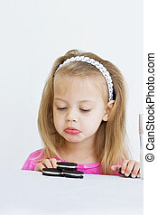 Child eating cookies - Cute little girl has cookie in hand,...