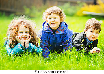 Happy children lying on grass and smiling.