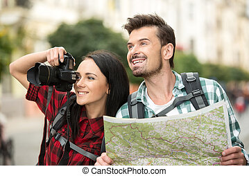 Tourists - Two young tourists with backpacks, touristic map...
