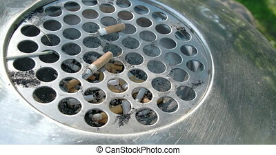 A cigarette bin or ahstray with lots of cigs inside. It is...