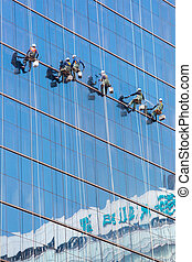High rise window washers - Laborers clean windows as a team...
