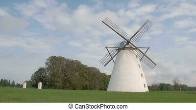 A classic old windmill in the middle of the field The white...