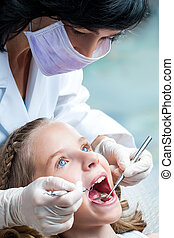 Female Dentist working on kids teeth.