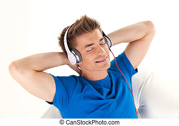Happy man in headphones relaxing on sofa at home. handsome...