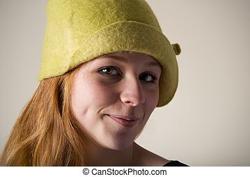 Close-up of smiling redhead in green hat