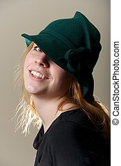Redhead in green hat with head tilted