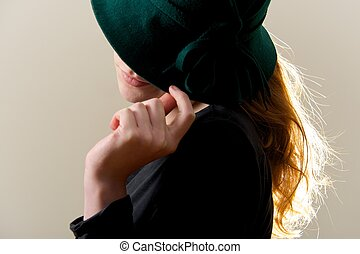 Backlit redhead hiding face behind green hat