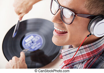 Young man working as dj with ear-phones and disc. closeup...