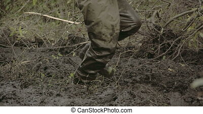 A man in boots walking onto the thick mud FS700 4K