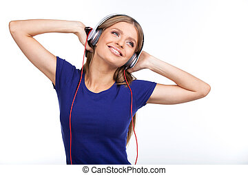 Cheerful young woman listening music with headphones. pretty brunette standing on white background and holding headphones
