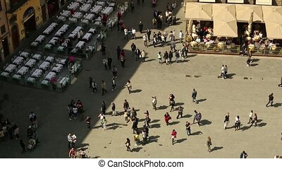 People walking in town square - Tourists and people walking...