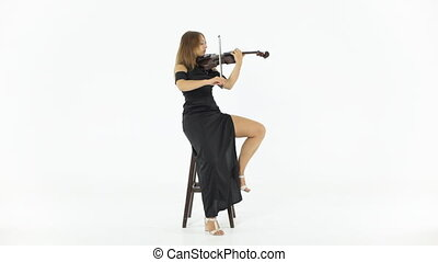 Young girl playing violin - Young girl sitting on a chair...