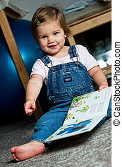Child view a book - Happy baby on the ground viewing a...