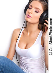 sexy babe in white shirt and headphones listening music. Beautiful girl sitting in headphones with eyes closed