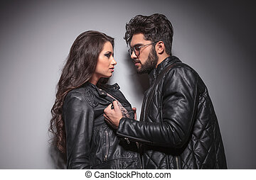 Young fashion couple face to face, the man is pulling his...
