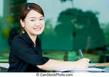 Asian business woman writing report - Young asian business...