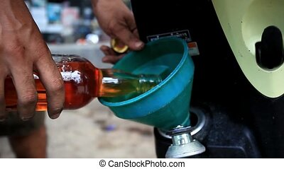 Pouring gasoline in the motorbike from bottle through a...