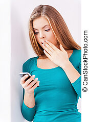 Shocking news Surprised beautiful young woman holding phone...