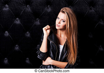 Glamour fashion model. Beautiful young woman with make up and hairstyle posing against black background