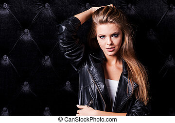 Cool and sexy. Beautiful young woman with make up and hairstyle posing against black background