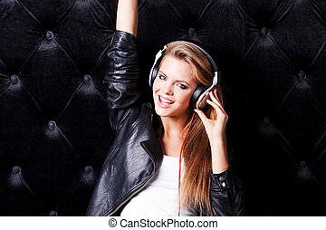 Musically taking fun. Beautiful young woman with make up and in headphones posing against black background