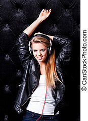 Music lover. Beautiful young woman with make up and in headphones posing against black background