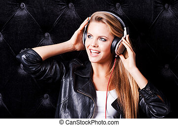 Listening to her favorite song. Beautiful young woman with make up and in headphones posing against black background