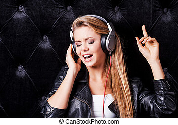 Beautiful young woman in headphones singing against black background