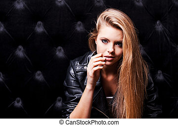 Seducing you. Beautiful young woman with make up and posing against black background