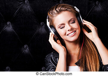 Amazing song! Beautiful young woman with make up and in headphones posing against black background