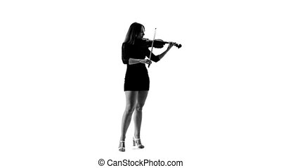 Silhouette of girl in a short black dress playing the violin...