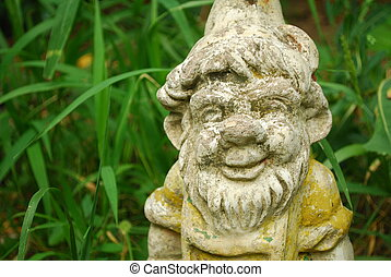 Garden Gnome - Old garden gnome standing between some plants...