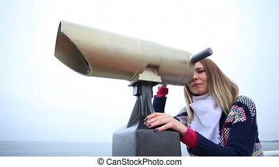 Woman looking through the binocular - Travel and tourism....
