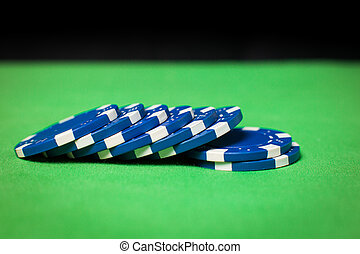 stack of poker chips on a green table - stack of blue poker...