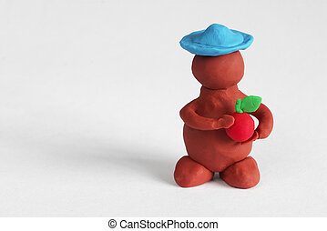 Plasticine man keeping a red apple over grey background