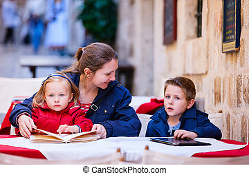 Family at outdoor cafe - Young mother and her two kids at...