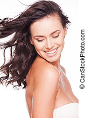 Natural beauty. Beautiful young woman looking at her shoulder and smiling while standing against white background