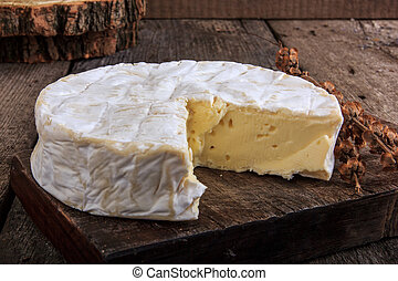 Camembert cheese on wooden cutting board in domestic...
