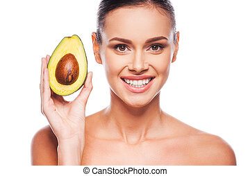 The multi talented avocado. Beautiful young shirtless woman holding avocado in her hand and smiling while standing against white background