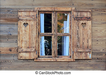 Window of a wooden hut with hearts in the blinds
