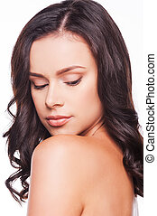 Natural beauty. Portrait of beautiful young woman looking at her shoulder while standing against white background