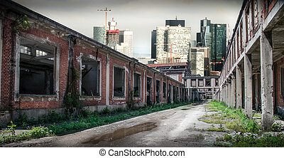 old and new - old abandoned factory in contrast with skyline
