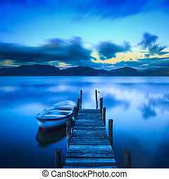 Wooden pier or jetty and a boat on a lake sunset Versilia...