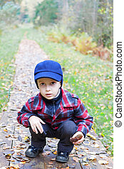 kid sitting forest road fall season clothes
