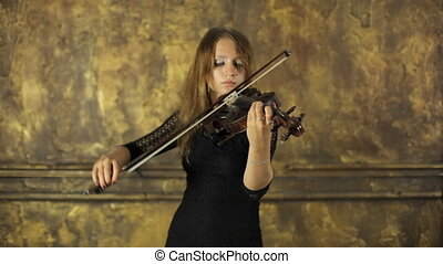 Beautiful girl in black dress playing the violin with inspiration
